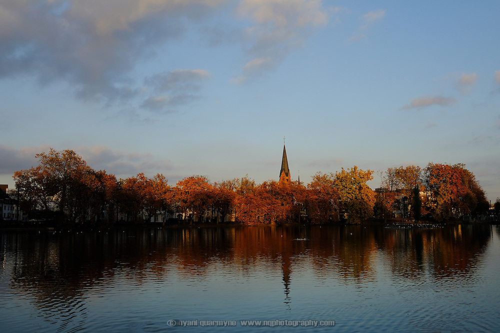 Autumn leaves and the spire of St Cecilia Church from across an ornamental pond at Schloss Benrath, a baroque pleasure palace, in Düsseldorf, Germany on 29 October 2016.