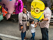 "12 SEPTEMBER 2016 - BANGKOK, THAILAND:  A family buys an inflatable ""Minion"" toy during the celebration of Eid al-Adha at Haroon Mosque in Bangkok. Eid al-Adha is also called the Feast of Sacrifice, the Greater Eid or Baqar-Eid. It is the second of two religious holidays celebrated by Muslims worldwide each year. It honors the willingness of Abraham to sacrifice his son, as an act of submission to God's command. Goats, sheep and cows are sacrificed in a ritualistic manner after services in the mosque. The meat from the sacrificed animal is supposed to be divided into three parts. The family retains one third of the share; another third is given to relatives, friends and neighbors; and the remaining third is given to the poor and needy.         PHOTO BY JACK KURTZ"
