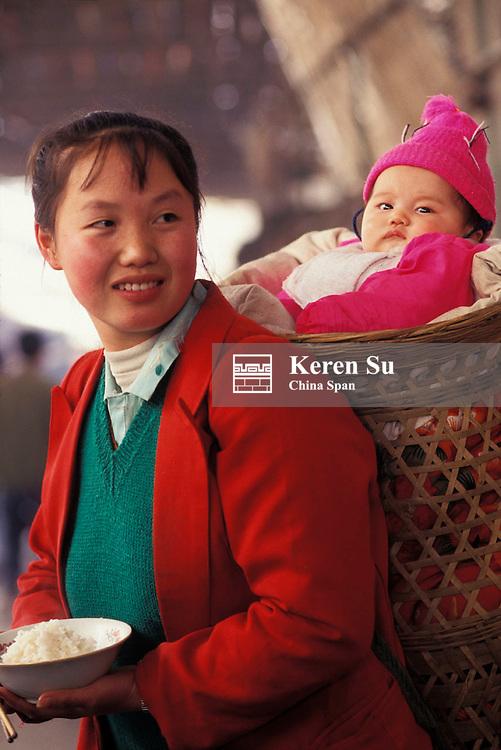 Woman carrying baby in basket, Chongqing, Sichuan Province, China