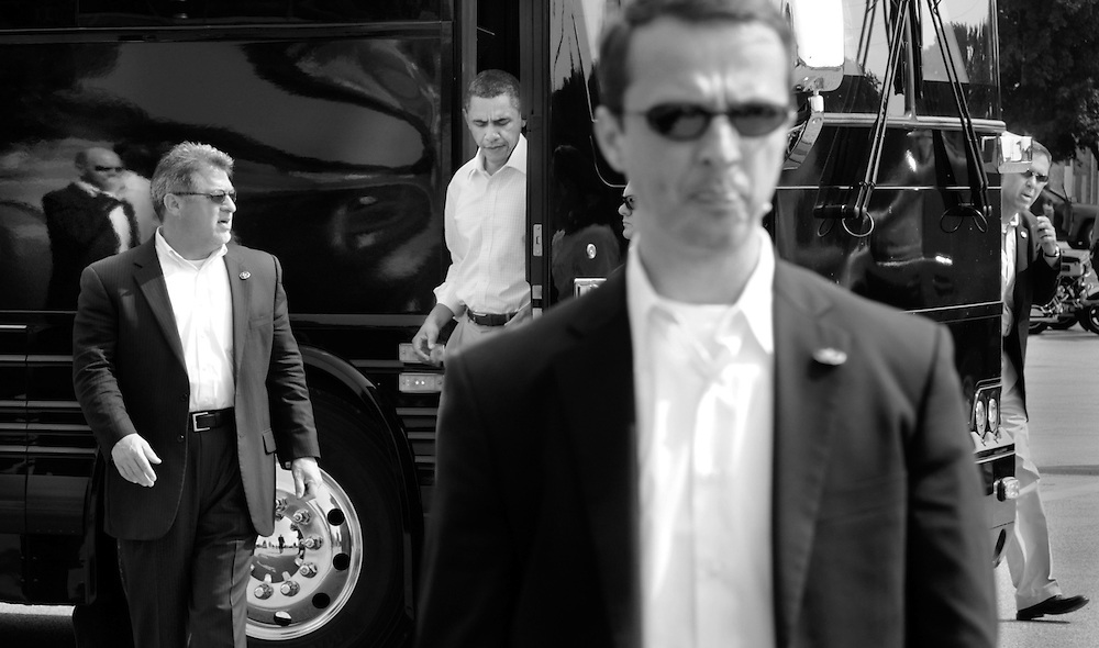 President Obama steps from his bus with the security detail on alert in Illinois.