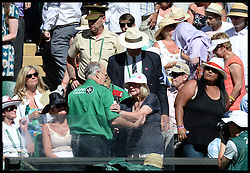 Image ©Licensed to i-Images Picture Agency. 03/07/2014. London, United Kingdom. A lady is helped out by medics as the heat gets to her on centre court as she watches the  ladies' Semi Final at Wimbledon. Picture by Andrew Parsons / i-Images
