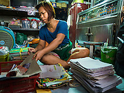 23 SEPTEMBER 2015 - BANGKOK, THAILAND: DAOLAOM SITTHIRUNG, 47, sorts through papers she has to keep or throw away before being evicted from her home near Wat Kalayanmit. Fifty-four homes around Wat Kalayanamit, a historic Buddhist temple on the Chao Phraya River in the Thonburi section of Bangkok, are being razed and the residents evicted to make way for new development at the temple. The abbot of the temple said he was evicting the residents, who have lived on the temple grounds for generations, because their homes are unsafe and because he wants to improve the temple grounds. The evictions are a part of a Bangkok trend, especially along the Chao Phraya River and BTS light rail lines. Low income people are being evicted from their long time homes to make way for urban renewal.           PHOTO BY JACK KURTZ