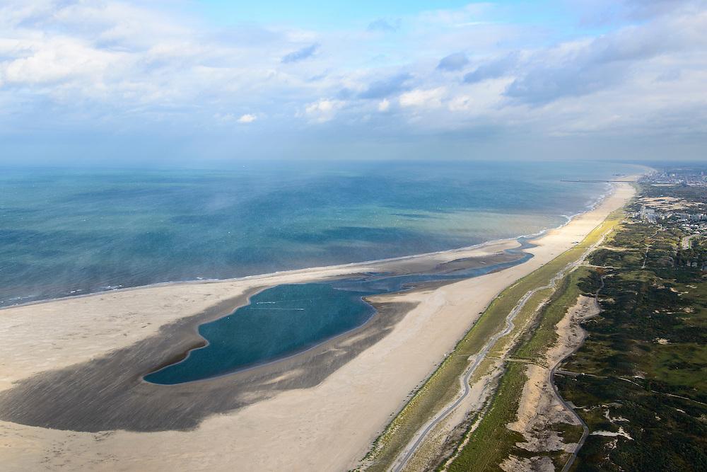 Nederland, Zuid-Holland, Gemeente Westland, 23-10-2013; Delflandse Kust ter hoogte van Ter Heijde en Monster, Scheveningen en Den Haag aan de horizon. Zandmotor, aanleg van kunstmatig schiereiland door het opspuiten van zand voor de kust. Wind, golven en stroming zullen het zand langs de kust verspreiden waardoor breder stranden en duinen ontstaan. De zandmotor is een experiment in het kader van kustonderhoud en kustverdediging. In de achtergrond de kassen van het Westland.<br /> Sand Engine, construction of artificial peninsula by the raising of sand for the coast of Ter Heijde (near the Hague, at the horizon). Wind, waves and currents will distribute the sand along the coast yielding wider beaches and dunes along the coastline. The Sand Engine is a experiment for coastal maintenance of coastal defense. In the background the Westland greenhouses.<br /> luchtfoto (toeslag op standard tarieven);<br /> aerial photo (additional fee required);<br /> copyright foto/photo Siebe Swart