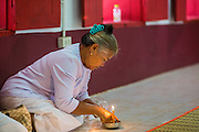 29 JUNE 2014 - DAN SAI, LOEI, THAILAND: A woman lights a candle during a ceremony in Wat Ponchai on the last morning of the Ghost Festival. Phi Ta Khon (also spelled Pee Ta Khon) is the Ghost Festival. Over three days, the town's residents invite protection from Phra U-pakut, the spirit that lives in the Mun River, which runs through Dan Sai. People in the town and surrounding villages wear costumes made of patchwork and ornate masks and are thought be ghosts who were awoken from the dead when Vessantra Jataka (one of the Buddhas) came out of the forest. On the last day of the festival people participate in merit making ceremonies at the Wat Ponchai in Dan Sai and lead processions through town soliciting donations for the temple.    PHOTO BY JACK KURTZ