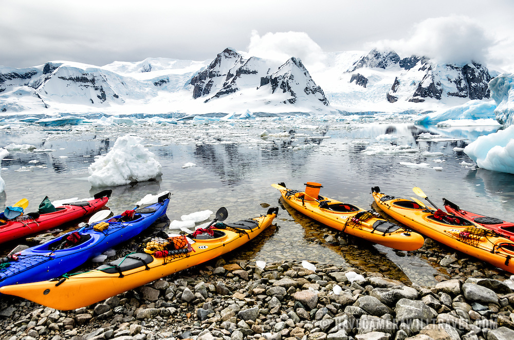 Brightly colored kayaks pulled up on the rocky shore at Cuverville Island on the Antarctic Peninsula.