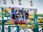 "14 AUGUST 2019 - DES MOINES, IOWA: A family rides the ""Crazy Mouse,"" a roller coaster type ride on the Midway at the Iowa State Fair. The Iowa State Fair is one of the largest state fairs in the U.S. More than one million people usually visit the fair during its ten day run. The 2019 fair run from August 8 to 18.               PHOTO BY JACK KURTZ"