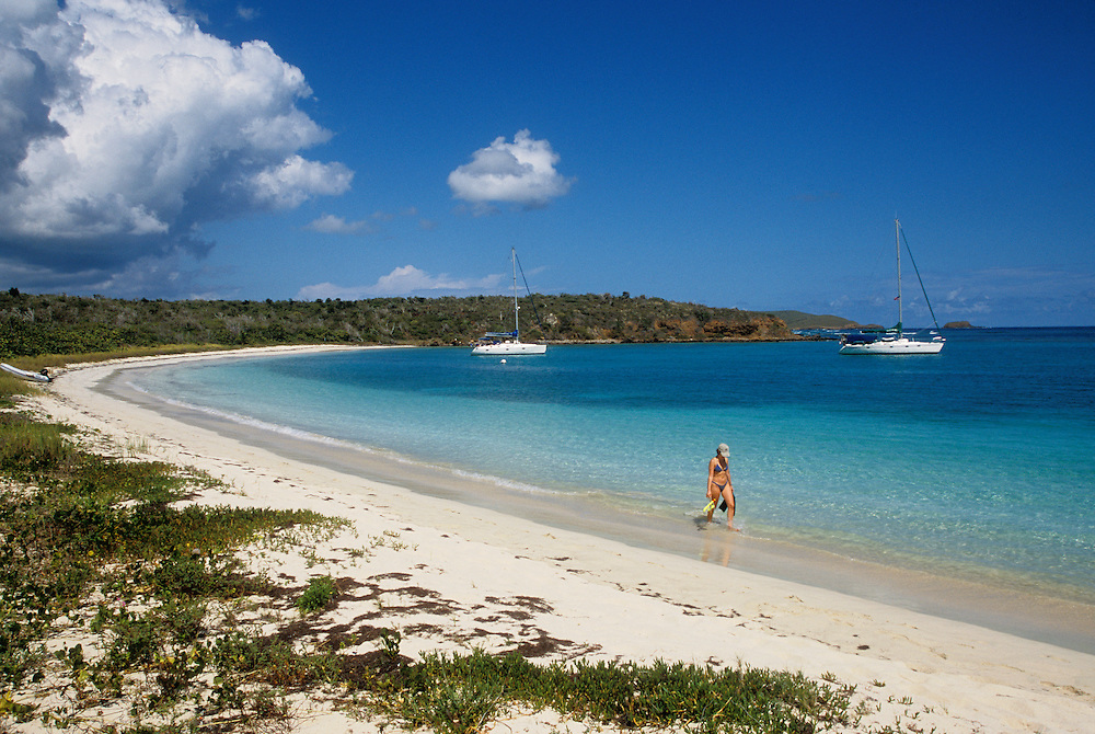 Woman with snorkeling gear walking on beach and yachts anchored in bay at Bahia des Tortugas; Culebra Island, Puerto Rico.