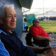"Merle Eberly watches a Clarinda A's baseball game from a shady spot under the team's locker room.  Merle, along with wife Pat have been the ""mom and pop"" of the team for 56 years.  Clarinda recently named the field after them."