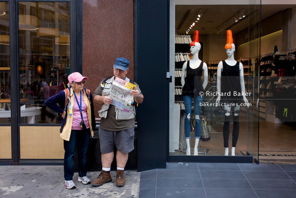 Two tourists in peak caps and two mannequins in matching headwear.