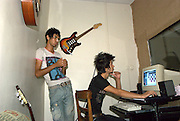 Pop artists edit a track in an underground studio.