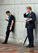 © Licensed to London News Pictures. 08/10/2012. Birmingham, UK Two men smoke cigarettes outside the conference centre on the day Chancellor of the Exchequer George Osborne gives his keynote conference speech at The Conservative Party Conference at the ICC today 8th October 2012. Photo credit : Stephen Simpson/LNP