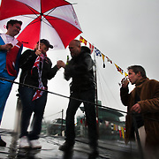 Rufus, ship owner at Hermitage Morrings by Tower Bridge and friends, enjoy champaigne in the driving rain. Celebrations in London, UK for Queen Elizabeth II Diamond Jubilee. 60 years as monarch in Britain.