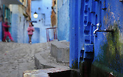 Fountain in a narrow street in the medina or old town of Chefchaouen in the Rif mountains of North West Morocco. Chefchaouen was founded in 1471 by Moulay Ali Ben Moussa Ben Rashid El Alami to house the muslims expelled from Andalusia. It is famous for its blue painted houses, originated by the Jewish community, and is listed by UNESCO under the Intangible Cultural Heritage of Humanity. Picture by Manuel Cohen