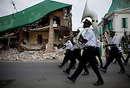 A band marches down the street next to the destroyed National Palace in downtown Port-au-Prince, Haiti, after playing the national anthem while the national flag is raised at the palace the morning of Friday, February 26, 2010.  This ritual happens every morning.