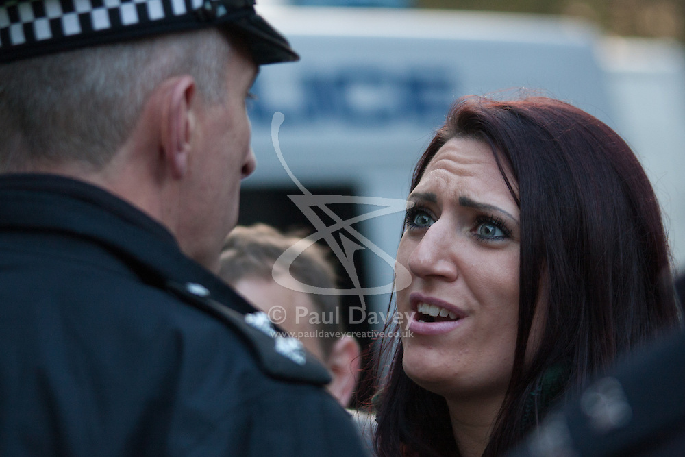 """Mayfair, London, November 28th 2014. A protest against Egypt's leader Al-Sisi descended into moinor scuffles as right wing """"patriots"""" from anti-Islamic group Britain First arrived to protest against the presence of Islamist preacher Anjem Choudary, who was recently arrestred as part of an ant-terror operation. Playing patriotic British Music, Britain First accused Muslims of worshiping a """"devil"""" and a """"paedophile prophet"""". Police had to intervene before hotheads on both sides became violent. PICTURED: Jayda Fransen, Deputy Leader of Britain First argues with a police officer who ordered her to turn down their music."""