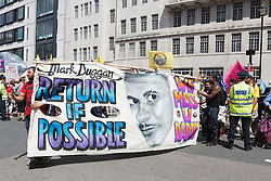 © Licensed to London News Pictures. 21/06/2014. London, England. Pictured: a large Mark Duggan banner is carried through the crowd. The No More Austerity demonstration & march takes place in Central London. It was organised by the People's Assembly and it is estimated that approx. 50,000 people joined the protest. Photo credit: Bettina Strenske/LNP