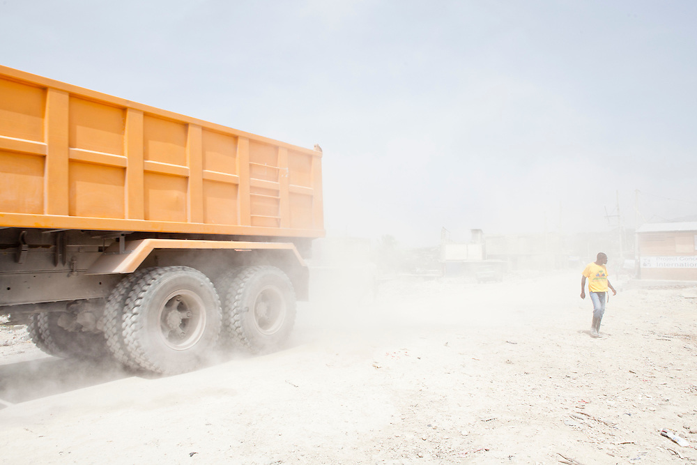 PORT-AU-PRINCE, HAITI - JULY 12: A dump truck kicks up dust as it passes through in the Fort National neighborhood on July 12, 2010 in Port-au-Prince, Haiti. Six months after an earthquake killed an estimated 230,000 people, many Haitians are struggling to rebuild their lives. (Photo by Brendan Hoffman/Getty Images) *** Local Caption ***