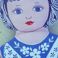 Vintage doll made from cloth or cotton material with face hair and dress all printed in blue red or pink inks