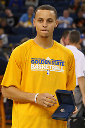 April 10, 2011; Oakland, CA, USA;  Golden State Warriors point guard Stephen Curry (left) is presented with his 2010 FIBA world championship ring before the game against the Sacramento Kings at Oracle Arena.