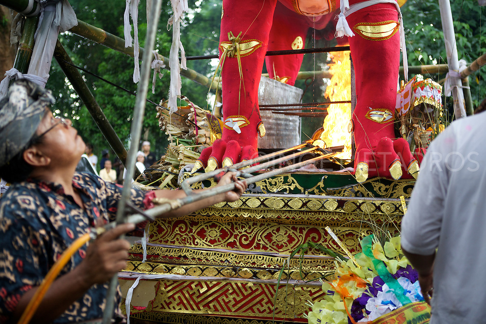 The first gas burner has been lit and put under the front of the red dragon.<br /> When a Balinese dies, it is believed that he must undergo certain rituals in order for his spirit to be released.<br /> The most important of the rituals is that of cremation, but it is so costly that many people either delay the ceremonies or go into massive debt to perform the rituals associated with the cremation.<br /> Before cremation, the body must be prepared for burial.<br /> The corpse is than buried for a certain period of time but no longer than 3 years.<br /> On the appointed time of the cremation, the family (or if several families cannot afford the cremation ceremony and rituals, a group cremation will occur and a cremation tower will be build and elaborate offerings will be prepared.<br /> Ubud, Bali 2013<br /> &copy;Ingetje Tadros www.ingetjetadros.com