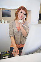 Young woman receptionist using the phone in the hairdressers