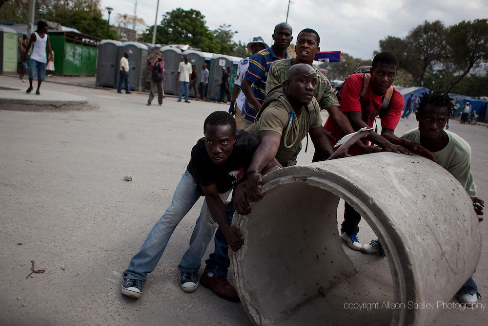 "Men prepare to roll a giant concrete pipe down the street at Haitian police as Haitians shouting ""Revolution"" took to the streets to demand that Haitian president Rene Preval leave office in Port-au-Prince, Haiti, February 7, 2011. Though he has parliamentary approval to stay in office until May 14, Preval's official mandate as president expires today.  Haitian elections were delayed-- first by the 2010 earthquake and then by the need for a run-off between challenging candidates."