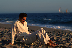 Man in deep thought sitting by the ocean during a sunset in California