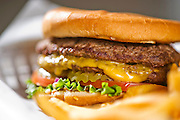A cheeseburger in a basket with french fries at Feltner Brothers Burgers in Fayetteville, Arkansas. Food photography from Feltner Brothers burgers and Franks in Fayetteville, Arkansas, for a magazine feature.