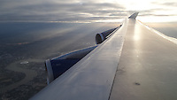 Wing of a British Airways Boeing 747 jumbo jet flying over London and the river Thames before landing at Heathrow Airport