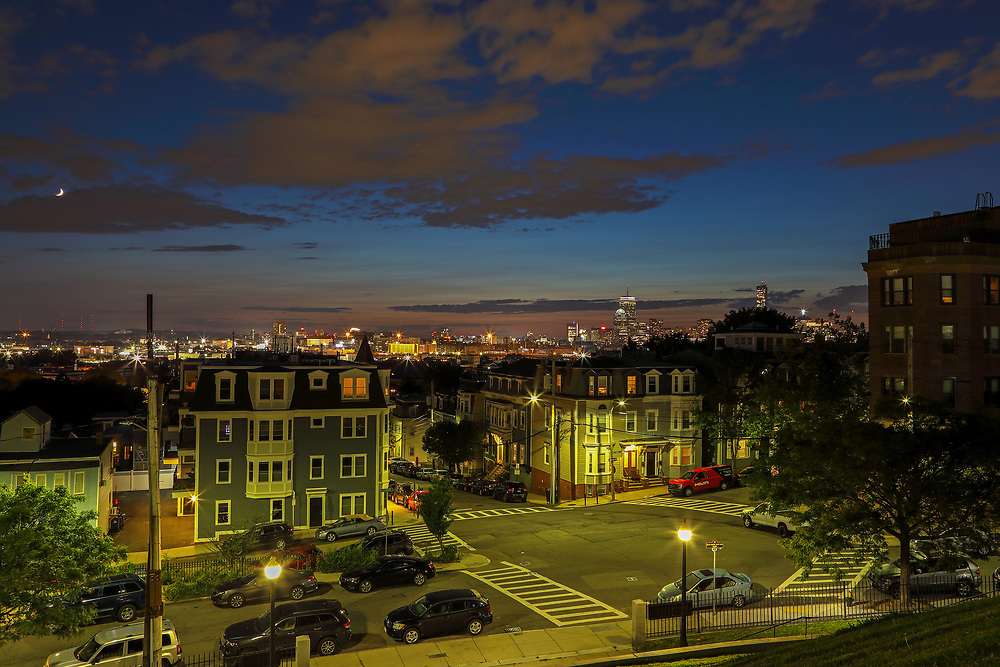 South Boston view of the Boston skyline at sunset showing parts of the Dorchester Heights neighborhood and the Beantown Hub in the backdrop.   <br />