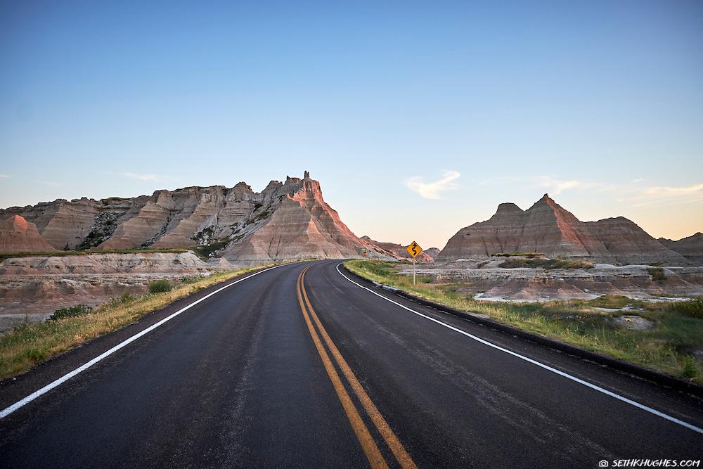 A highway enters the colorful hills of Badlands National Park, South Dakota