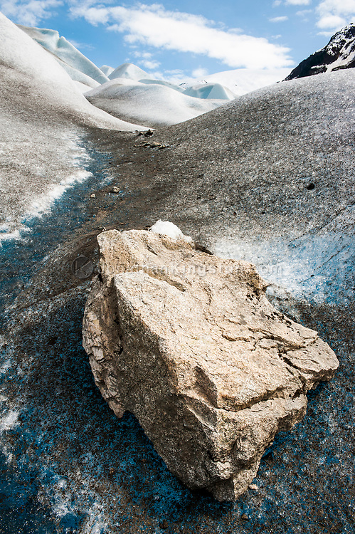 A glacial erratic next to a glacial meltwater stream on a glacier.