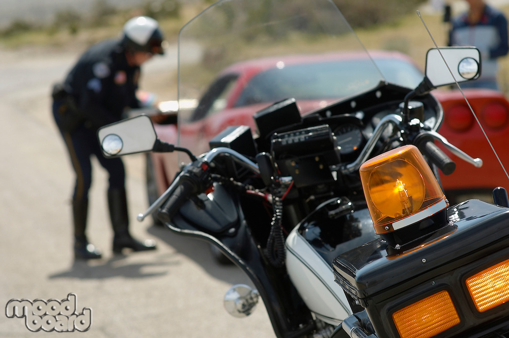 Traffic cop talking with car driver, focus on motorcycle in foreground