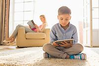 Boy using digital tablet on floor with mother reading magazine in background