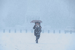 © Licensed to London News Pictures. 27/02/2018. London, UK. A woman shelters underneath an umbrella from heavy snow on Horse Guards Parade in central London. Severe cold, blizzards and heavy snow are expected for the rest of the week as the 'Beast from the East' brings freezing Siberian air to the UK. Photo credit: Rob Pinney/LNP