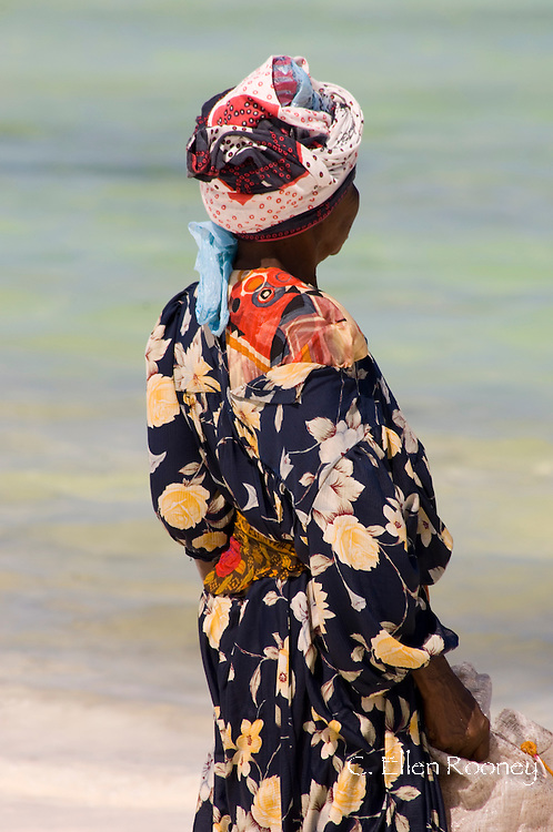 A local woman in colourful dress with her bag of harvested seaweed.  Paje, Zanzibar<br /> Tanzania