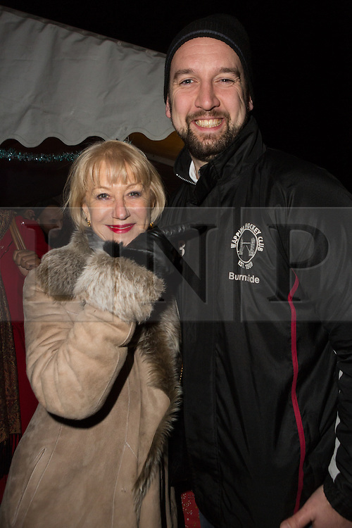© Licensed to London News Pictures. 08/12/2014. London, UK. Helen Mirren poses for a photograph with the Chairman of Wapping Hockey Club, Stuart Burnside. Dame Helen Mirren turns on the Christmas tree lights at Wapping Green in Tower Hamlets, East London tonight. This is the first time in many years that Wapping has had a Christmas tree and Dame Helen Mirren surprised residents by turning up at the community event and leading the countdown to switching the tree lights on. She then joined residents singing carols and drinking mulled wine, at the event which was arranged by the local councillor for Wapping and St Katharines, Julia Dockerill. Photo credit : Vickie Flores/LNP