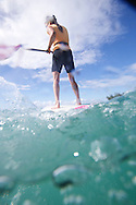 In the water shot of SUP paddlers heading away mid-stroke in on the North Shore of Hawaii in the winter