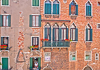 Detail of a beautiful brick facade with oriental windows, balconies and flowers in Venice, Italy.