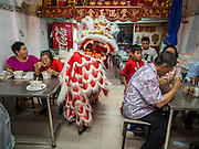 """19 FEBRUARY 2015 - BANGKOK, THAILAND: A lion dance troupe solicits donations in a Chinese restaurant on Chinese New Year in the Chinatown district of Bangkok. 2015 is the Year of Goat in the Chinese zodiac. The Goat is the eighth sign in Chinese astrology and """"8"""" is considered to be a lucky number. It symbolizes wisdom, fortune and prosperity. Ethnic Chinese make up nearly 15% of the Thai population. Chinese New Year (also called Tet or Lunar New Year) is widely celebrated in Thailand, especially in urban areas that have large Chinese populations.    PHOTO BY JACK KURTZ"""
