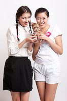 Portrait of young female friends with puppy against white background