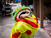 07 APRIL 2017 - BANGKOK, THAILAND:  A boy who lives in Pom Mahakan walks through the old fort in a Chinese Lion Dance outfit. The final evictions of the remaining families in Pom Mahakan, a slum community in a 19th century fort in Bangkok, have started. City officials are moving the residents out of the fort. NGOs and historic preservation organizations protested the city's action but city officials did not relent and started evicting the remaining families in early March.             PHOTO BY JACK KURTZ
