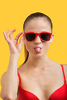 Portrait of young woman in sunglasses sticking out tongue over yellow background