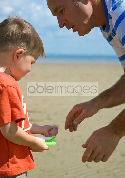 Father talking to young boy holding kite flying line