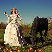 Blonde young woman in period costume standing outdoors with apples spilling out of basket onto grass next to horse