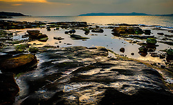 Evening light on the rocks at Skate Bay on the west coast of the island of Great Cumbrae, Scotland.  The Isle of Bute can be seen in the background.<br /> <br /> (c) Andrew Wilson | Edinburgh Elite media