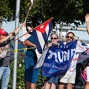 Cuban Americans supporters of President Trump wave flags and signs as his motorcade goes by them. Trump arrived for his third weekend in a row to his winter White House Mar-a-Lago in Palm Beach.<br /> Photography by Jose More