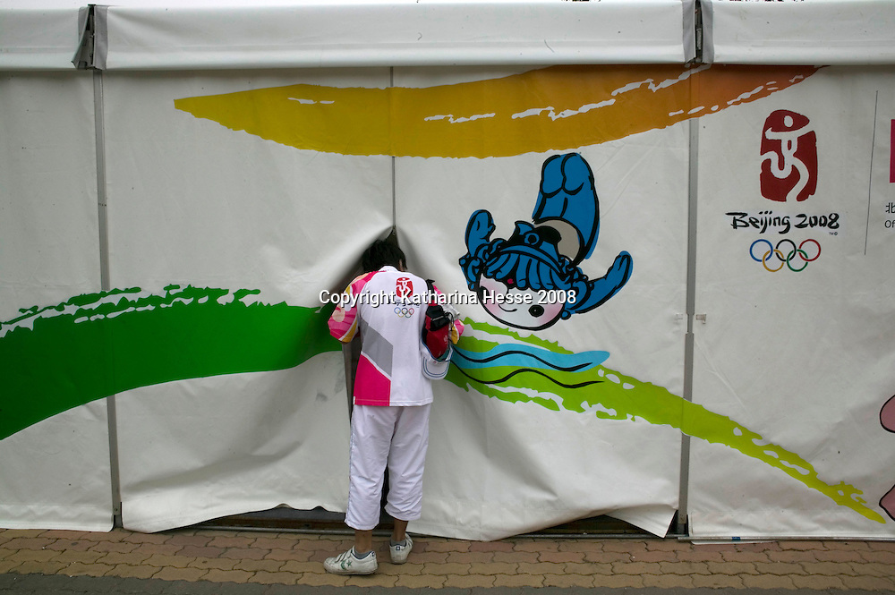BEIJING, AUGUST 6 :  a volunteer peeps into a tent in one of public places where Beijingers can watch live broadcasts of the Olympic Games.