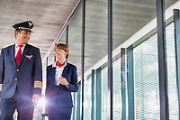 Portrait of mature pilot walking with young attractive stewardess in airport