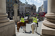 Mounted City Police officers make their presence known while on their horses in spring sunshine at Royal Exchange in the heart of the capital's financial district, on 19th April, in the City of London, England.